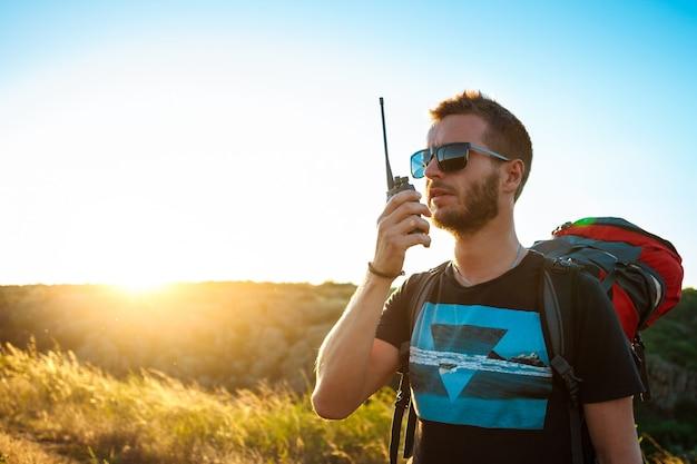 Jovem bonito falando no rádio walkie-talkie, apreciando a vista do canyon