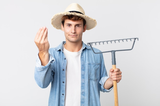 Jovem bonito fazendo capice ou gesto de dinheiro, dizendo para você pagar. conceito de fazendeiro