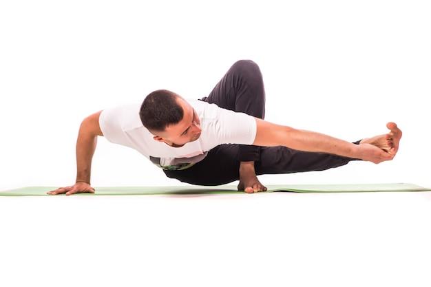 Jovem bonito fazendo pose de ioga isolada em um fundo branco