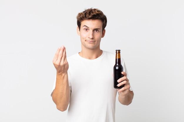 Jovem bonito fazendo um gesto de capice ou dinheiro, dizendo para você pagar e segurando uma garrafa de cerveja