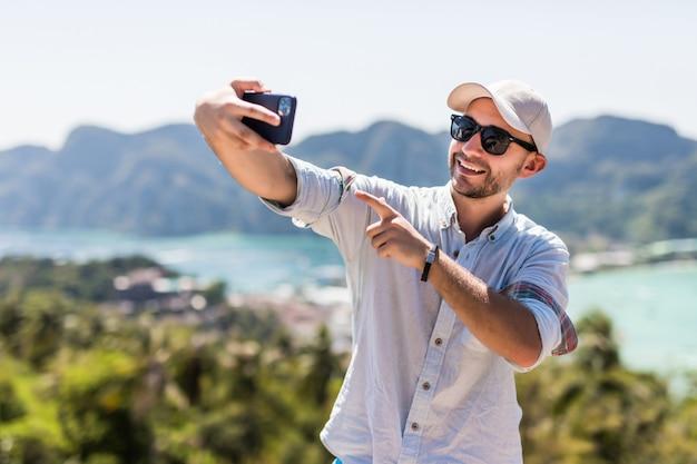 Jovem bonito fazer vídeo chamada no telefone, apreciando a vista no ponto de vista da ilha de phi phi. conceito de férias de verão.