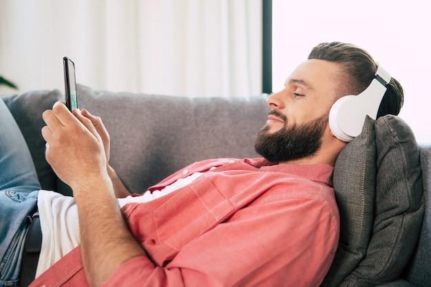 Jovem bonito feliz barbudo de óculos e fones de ouvido está ouvindo sua música favorita no smartphone enquanto relaxa no sofá em casa