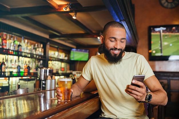 Jovem bonito feliz bebendo cerveja em bar e usando smartphone
