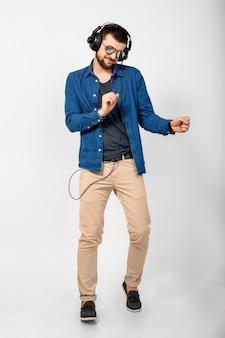 Jovem bonito feliz e sorridente dançando e ouvindo música em fones de ouvido isolados no fundo branco do estúdio, vestindo camisa jeans e óculos escuros
