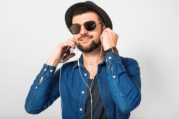Jovem bonito feliz e sorridente ouvindo música em fones de ouvido isolados no fundo branco do estúdio, segurando o smartphone, vestindo camisa jeans, chapéu e óculos escuros