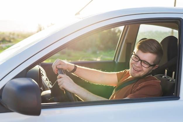 Jovem bonito feliz em uma camiseta marrom dirigindo um carro