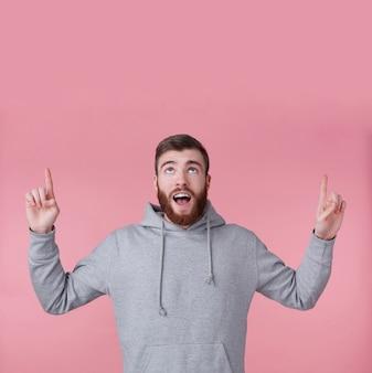 Jovem bonito feliz espantado homem barbudo vermelho com capuz cinza, parece surpreso, fica sobre um fundo rosa com boca e olhos bem abertos, quer chamar sua atenção e aponta para cima para copiar o espaço.