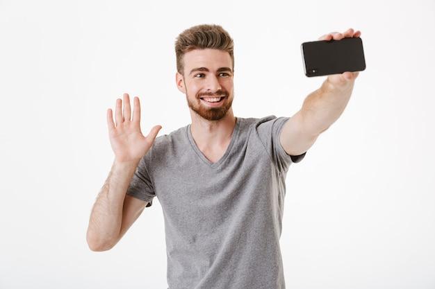 Jovem bonito feliz fazer selfie falando por aceno de telefone móvel.