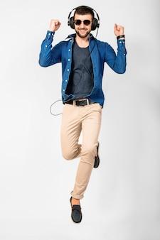 Jovem bonito feliz sorridente dançando e ouvindo música em fones de ouvido isolados no fundo branco do estúdio, vestindo camisa jeans e óculos escuros. o vencedor pulando com sucesso