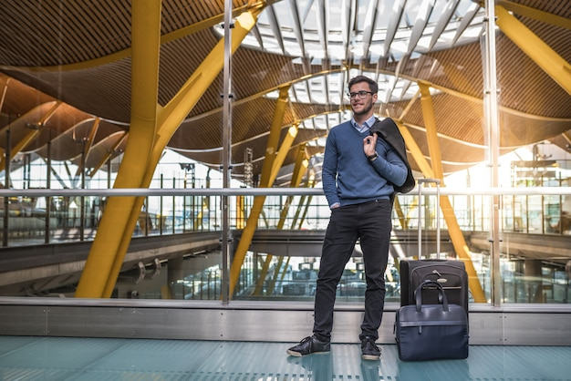 Jovem bonito feliz sorrindo no aeroporto esperando seu voo com bagagem