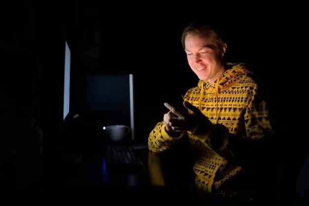 Jovem bonito feliz usando o telefone enquanto trabalhava horas extras em casa no escuro