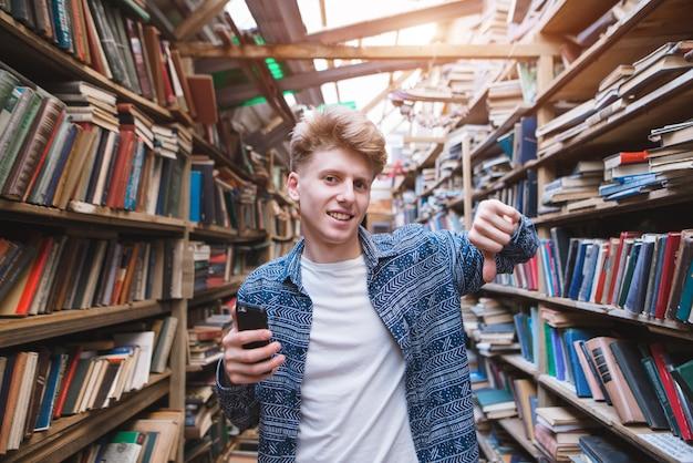 Jovem bonito fica em uma biblioteca com um smearphone na mão e mostra o dedo para baixo.