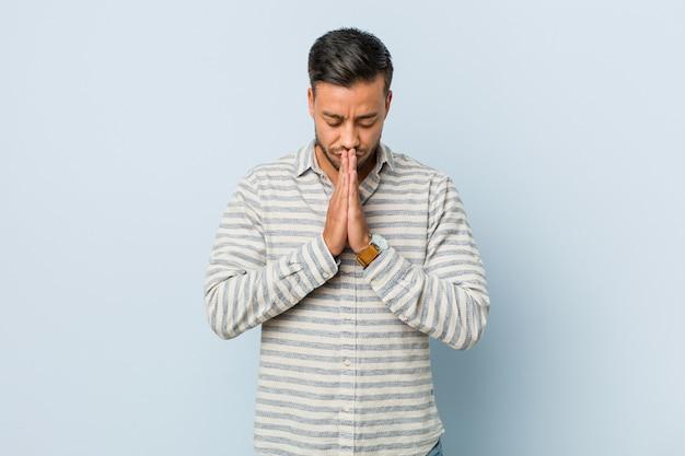 Jovem bonito filipino de mãos dadas para orar perto da boca, sente-se confiante.