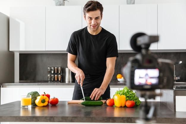 Jovem bonito filmando seu episódio de blog de vídeo