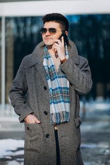 Jovem bonito fora usando o telefone