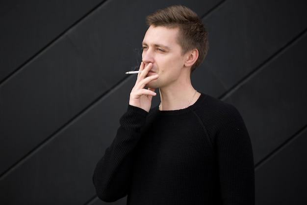 Jovem bonito fumando um cigarro em fundo preto