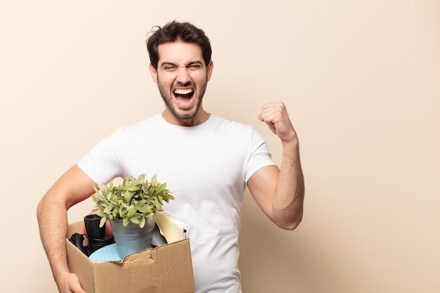 Jovem bonito gritando agressivamente com uma expressão de raiva ou com os punhos cerrados celebrando o sucesso