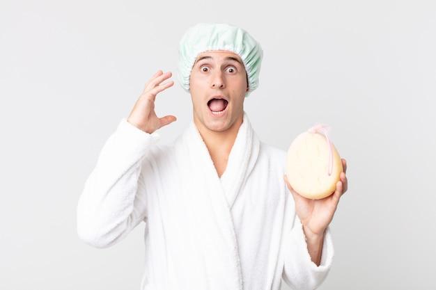 Jovem bonito gritando com as mãos ao alto com um roupão de banho, touca de banho e uma esponja