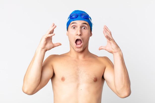 Jovem bonito gritando com as mãos no ar. conceito de nadador