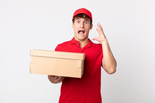 Jovem bonito gritando com as mãos no conceito de serviço de pacote de entrega de ar.