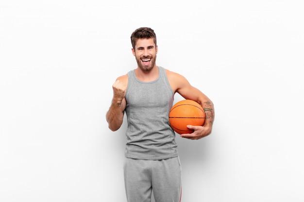 Jovem bonito gritando triunfantemente, rindo e se sentindo feliz e animado enquanto celebra o sucesso segurando uma bola de basquete.