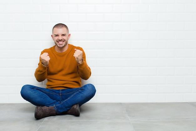 Jovem bonito gritando triunfantemente, rindo e se sentindo feliz e animado enquanto festeja o sucesso sentado no chão