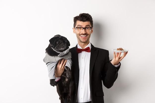 Jovem bonito hippie de terno e óculos segurando um pug preto fofo e ração para animais de estimação no prato, em pé sobre um fundo branco