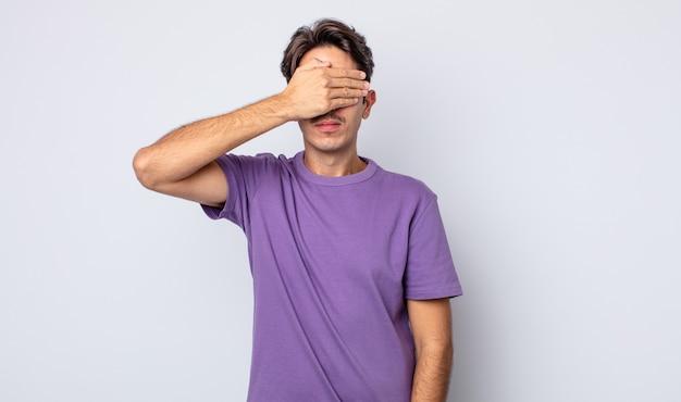 Jovem bonito hispânico cobrindo os olhos com uma das mãos, sentindo-se assustado ou ansioso, imaginando ou cegamente esperando por uma surpresa