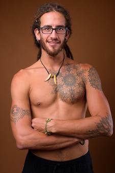 Jovem bonito hispânico com dreadlocks sem camisa contra o br
