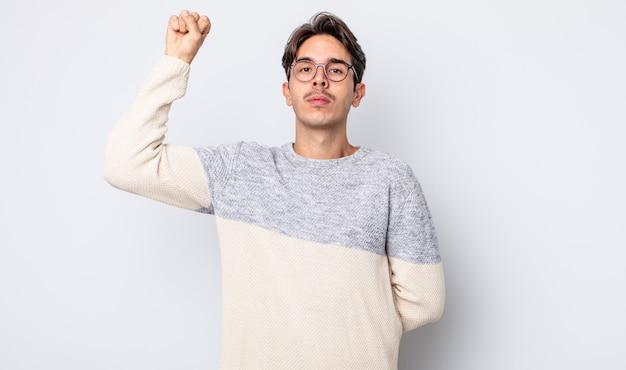 Jovem bonito hispânico se sentindo sério, forte e rebelde, levantando o punho, protestando ou lutando pela revolução