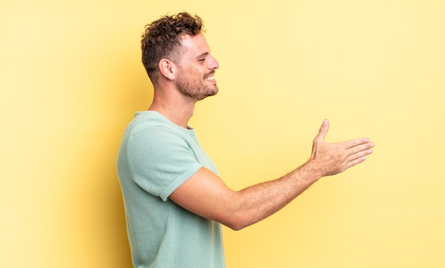 Jovem bonito hispânico sorrindo, cumprimentando você e oferecendo um aperto de mão para fechar um negócio de sucesso, o conceito de cooperação