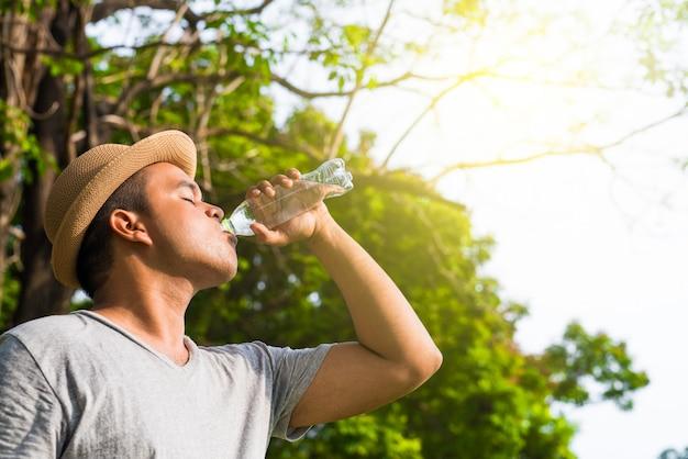 Jovem bonito homem asiático bebendo água