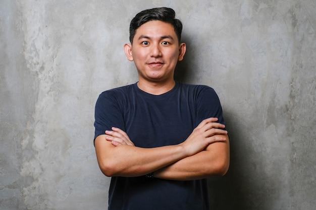 Jovem bonito homem asiático vestindo camiseta casual sobre o rosto feliz do fundo da parede de concreto, sorrindo com os braços cruzados, olhando para a câmera. pessoa positiva.