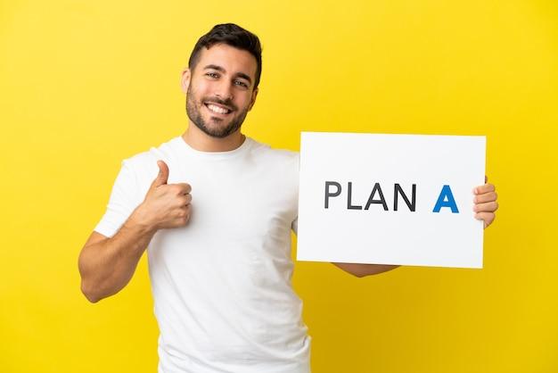 Jovem bonito homem caucasiano isolado em um fundo amarelo segurando um cartaz com a mensagem plano a com o polegar para cima