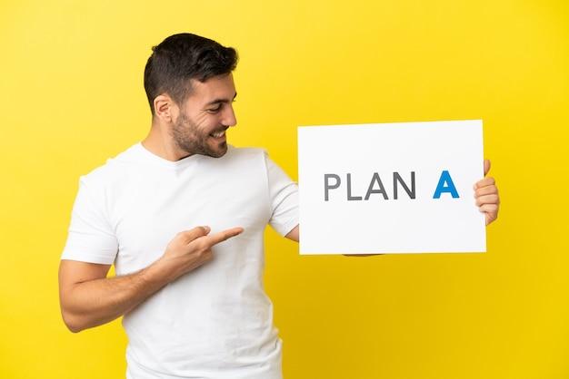Jovem bonito homem caucasiano isolado em um fundo amarelo segurando um cartaz com a mensagem plano a e apontando-o