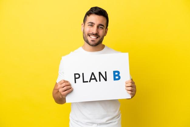 Jovem bonito homem caucasiano isolado em um fundo amarelo segurando um cartaz com a mensagem plano b com expressão feliz