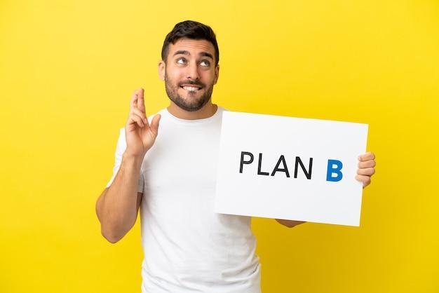 Jovem bonito homem caucasiano isolado em um fundo amarelo segurando um cartaz com a mensagem plano b cruzando os dedos