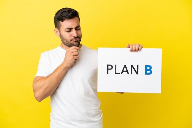 Jovem bonito homem caucasiano isolado em um fundo amarelo segurando um cartaz com a mensagem plano b e pensando