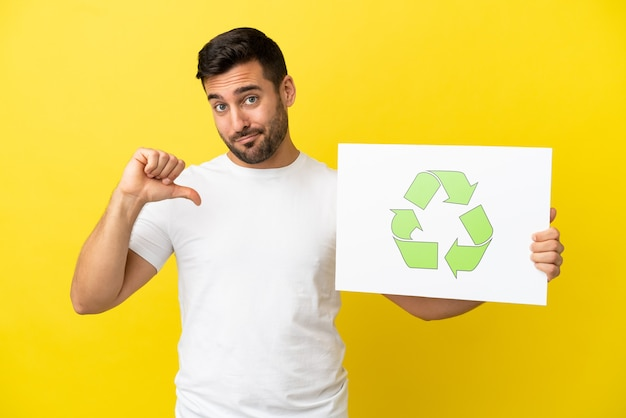 Jovem bonito homem caucasiano isolado em um fundo amarelo segurando um cartaz com o ícone de reciclagem e um gesto orgulhoso