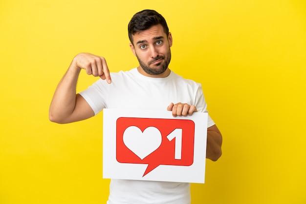 Jovem bonito homem caucasiano isolado em um fundo amarelo segurando um cartaz com o ícone de semelhante e apontando-o