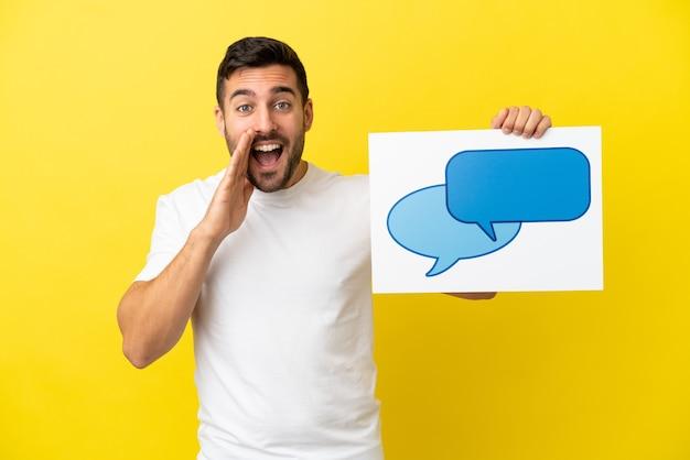 Jovem bonito homem caucasiano isolado em um fundo amarelo segurando um cartaz com o ícone de um balão de fala e gritando