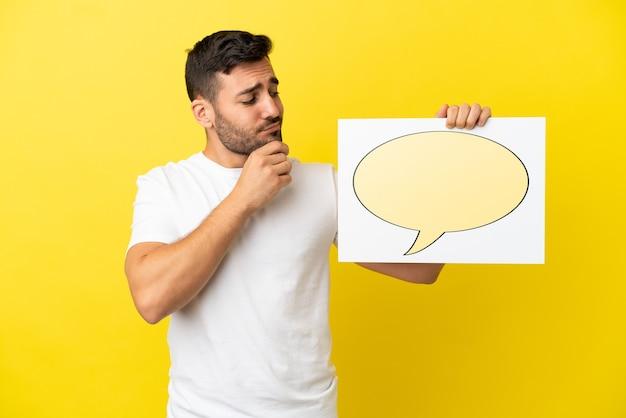 Jovem bonito homem caucasiano isolado em um fundo amarelo segurando um cartaz com o ícone de um balão de fala e pensando