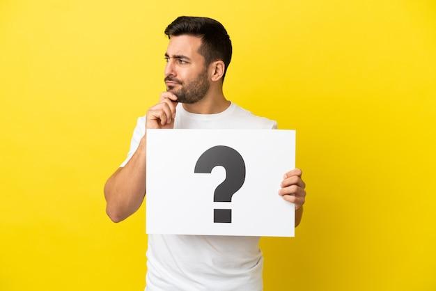 Jovem bonito homem caucasiano isolado em um fundo amarelo segurando um cartaz com o símbolo de ponto de interrogação e pensando