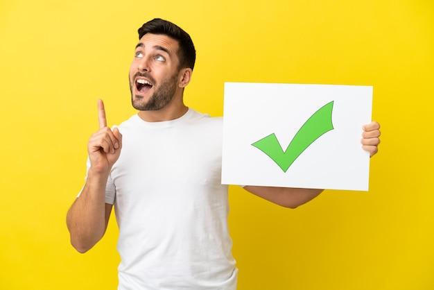 Jovem bonito homem caucasiano isolado em um fundo amarelo segurando um cartaz com o texto ícone de marca de seleção verde e pensando