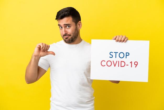 Jovem bonito homem caucasiano isolado em um fundo amarelo segurando um cartaz com o texto pare covid 19 com um gesto orgulhoso