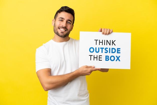 Jovem bonito homem caucasiano isolado em um fundo amarelo segurando um cartaz com o texto pense fora da caixa com uma expressão feliz