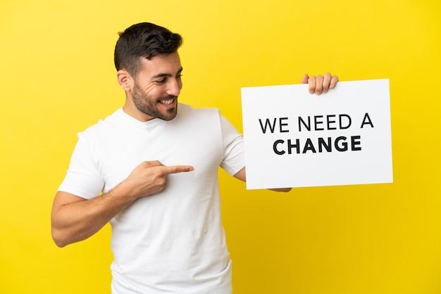 Jovem bonito homem caucasiano isolado em um fundo amarelo segurando um cartaz com o texto precisamos de uma mudança e apontando-o