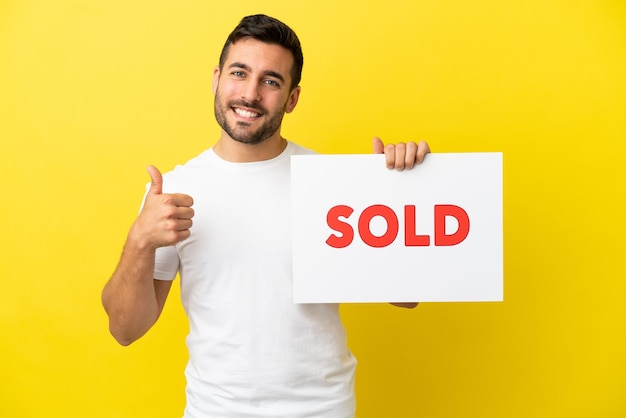 Jovem bonito homem caucasiano isolado em um fundo amarelo segurando um cartaz com o texto vendido com o polegar para cima
