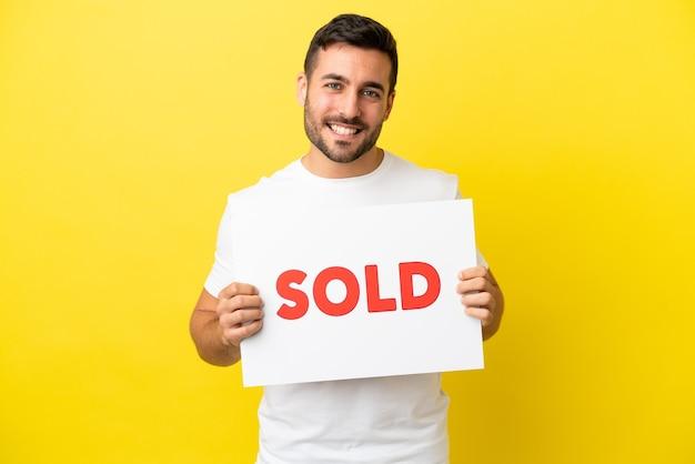 Jovem bonito homem caucasiano isolado em um fundo amarelo segurando um cartaz com o texto vendido com uma expressão feliz