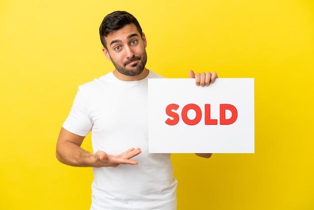 Jovem bonito homem caucasiano isolado em um fundo amarelo segurando um cartaz com o texto vendido e apontando-o